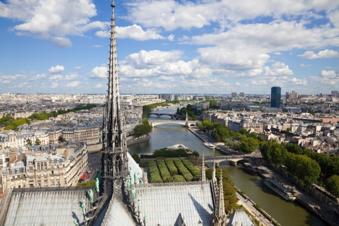 Notre Dame: The Spire overlooking the skyline of Paris
